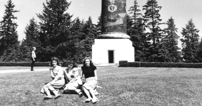 Three girls sit at the base of the Astoria Column in the 1940s