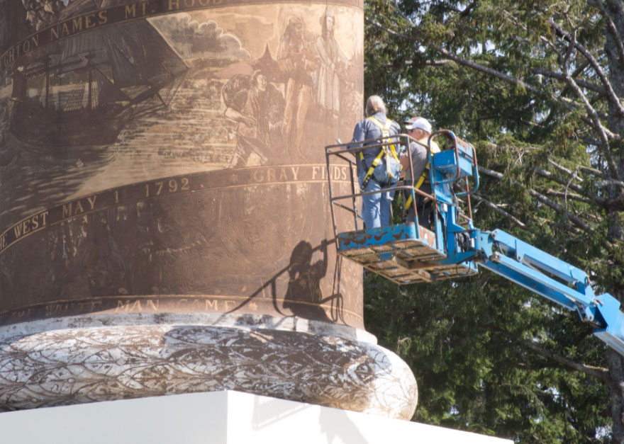 A restoration crew on a lift discusses their work on the Astoria Column